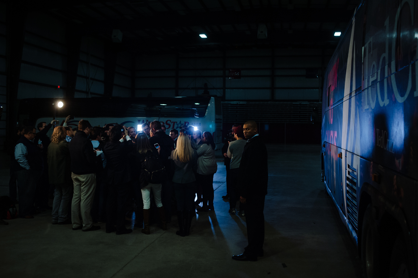 A private security guard watches as Republican U.S. presidential candidate Ted Cruz' holds a media availability before an event in Spencer, Iowa on January 6, 2016.