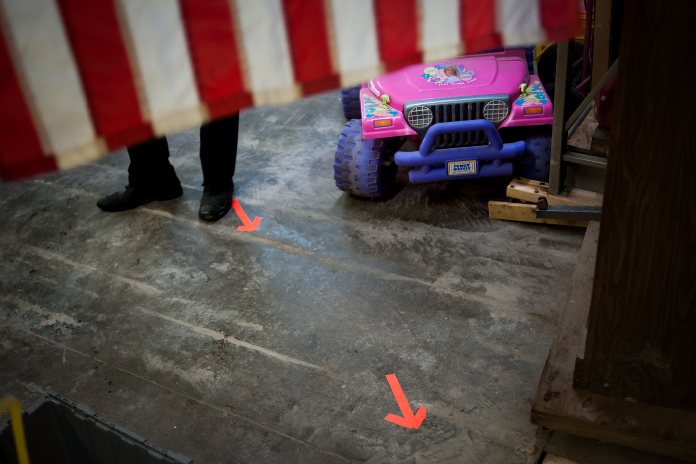 A member of Democratic U.S. presidential candidate Bernie Sanders' staff awaits his arrival as arrows point his path toward the microphone at an event in a garage in Charles City, Iowa on January 30, 2016.