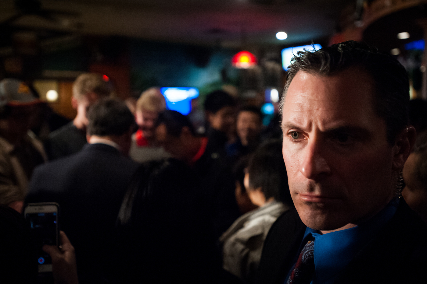 A member of the New Jersey State Police Executive Protection Unit watches over the crowd as Republican presidential candidate New Jersey Governor Chris Christie greets supporters after a town hall event at Mickey's Irish Pub in Waukee, Iowa on December 30, 2015.