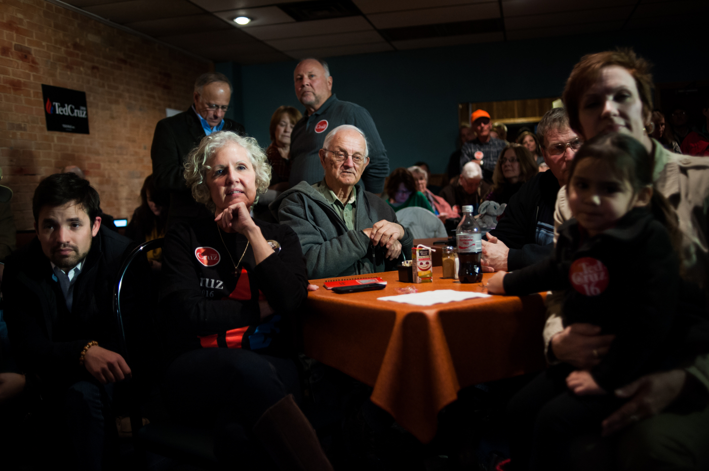 Supporters listen as Republican U.S. presidential candidate Ted Cruz does a live television interview ahead of his campaign stop at Prime Time Restaurant in Guthrie Center, Iowa on January 4, 2016.