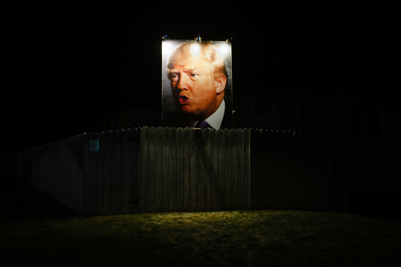 A photo of Republican U.S. presidential candidate Donald Trump stands over the fence at the home of George Davey, a formerly registered independent turned Republican Trump supporter. Davey puts up signage every election at his home off Jordan Creek Parkway and Pommel Place in Des Moines, Iowa.