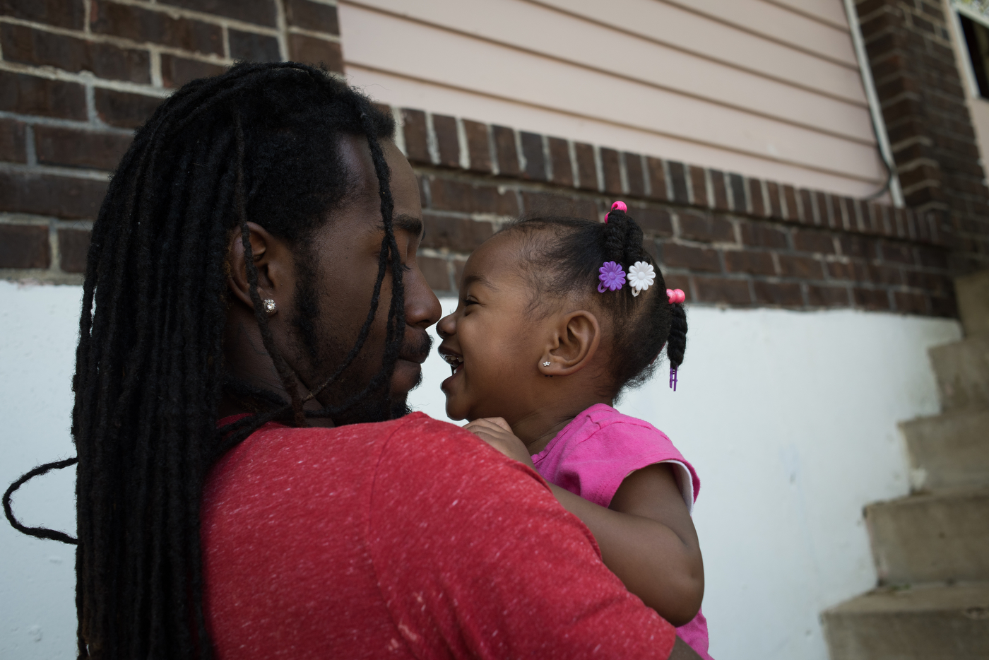 """Raymond """"Trip"""" Williams plays with his 18-month-old daughter Rayne at his grandmother's house in Ferguson, Mo. Trip, who is separated from Rayne's mother, recently secured a job in an effort to provide for his daughter better, motivated by seeing some of his friends grow up without both parents around."""