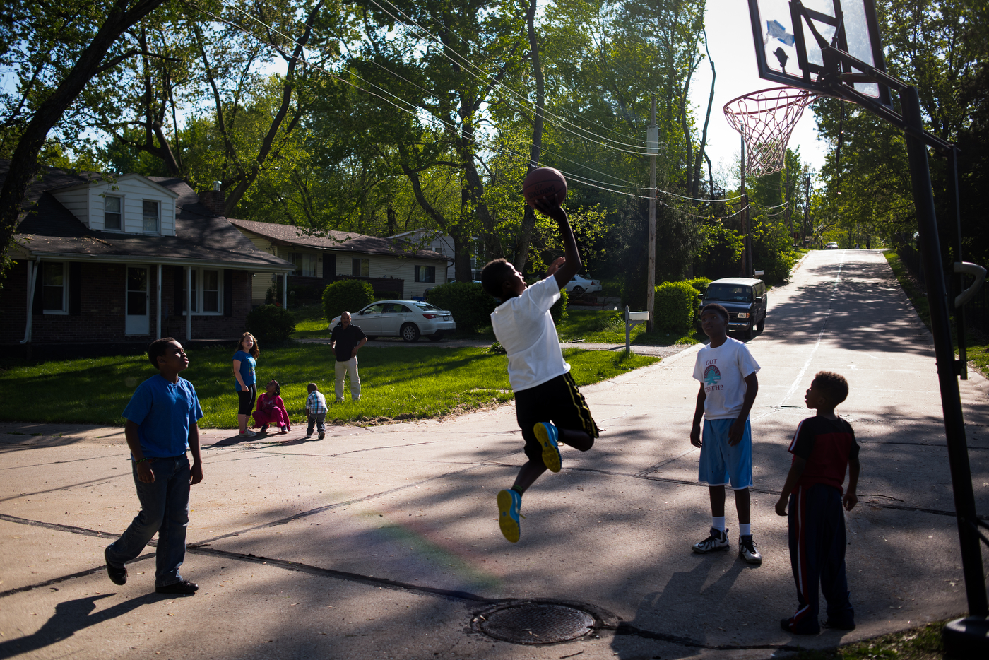 """Kids play basketball on the corner of Halpin Drive and Lagonda Avenue where a young man named Demetrius """"Trap"""" Stegall was killed in 2009. Trap was involved in a robbery and after a large group argument earlier that day, an associate of the person who was robbed returned to the corner and opened fire."""