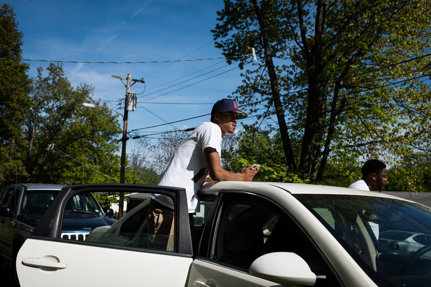 TJ Banks surveys the street while hanging out with friends in the Bermuda neighborhood of Ferguson, Mo. Banks stopped attending college because of high costs but was hoping to save up money to return to school.