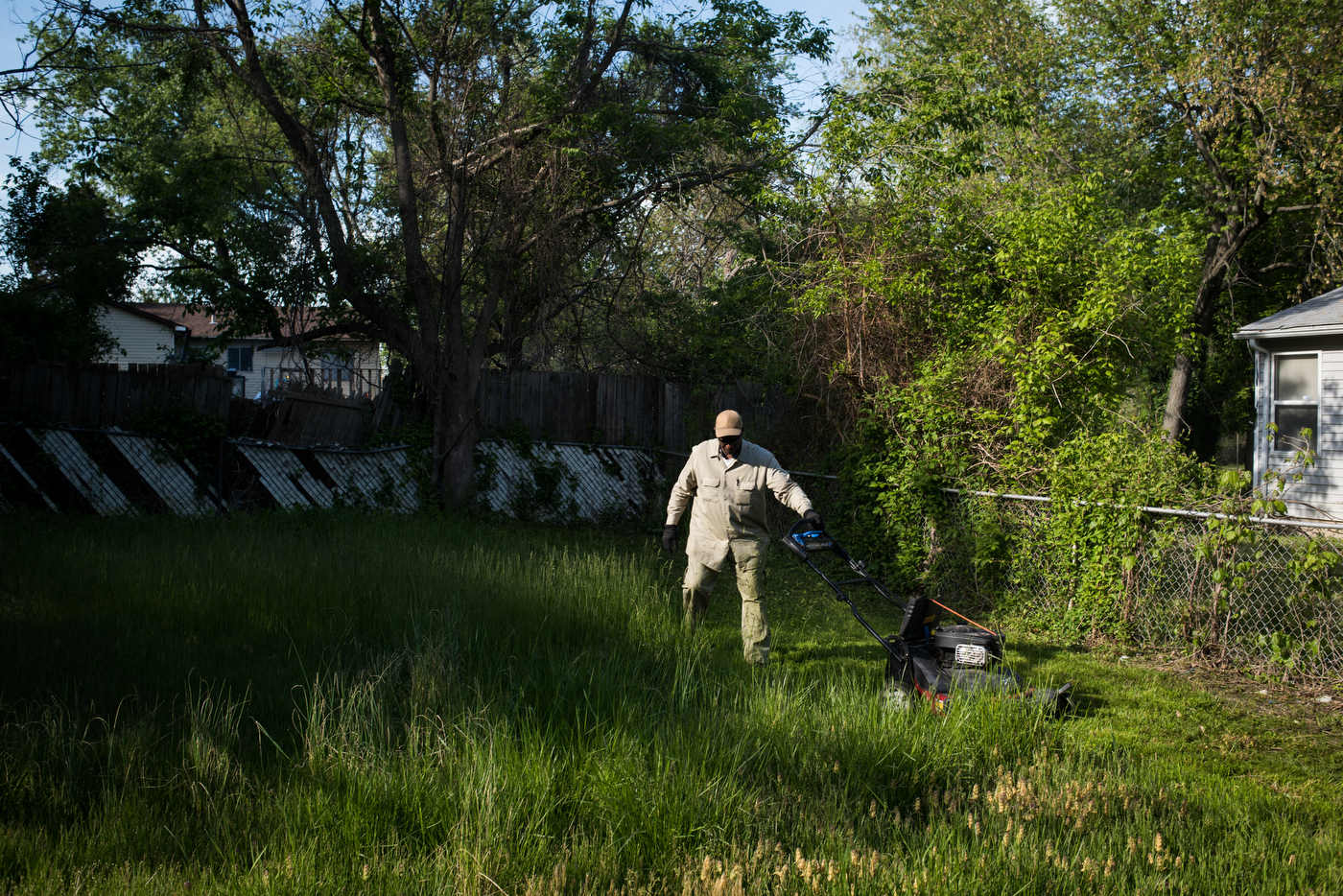 """Richard clears an overgrown yard of a rental house in the Bermuda neighborhood of Ferguson, Mo. Code enforcement officers are a common sight in the neighborhood and ticket people for long lawns and many discretionary violations like """"disturbing the peace."""" Code enforcement accounted for $2.46 million dollars of the city's budget in 2013."""