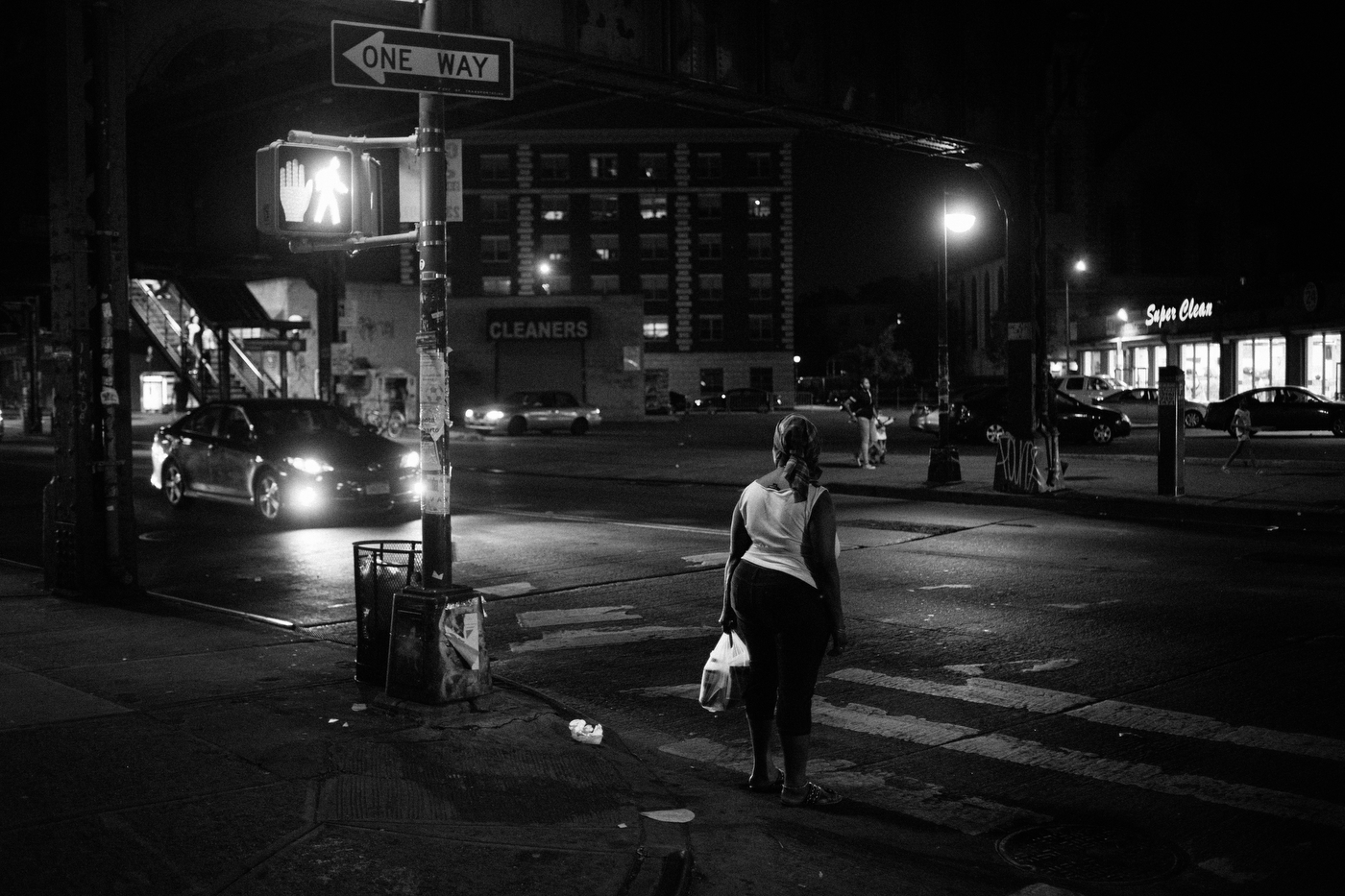 A woman waits to cross Broadway toward Bedford-Stuyvesant from Bushwick, NY.