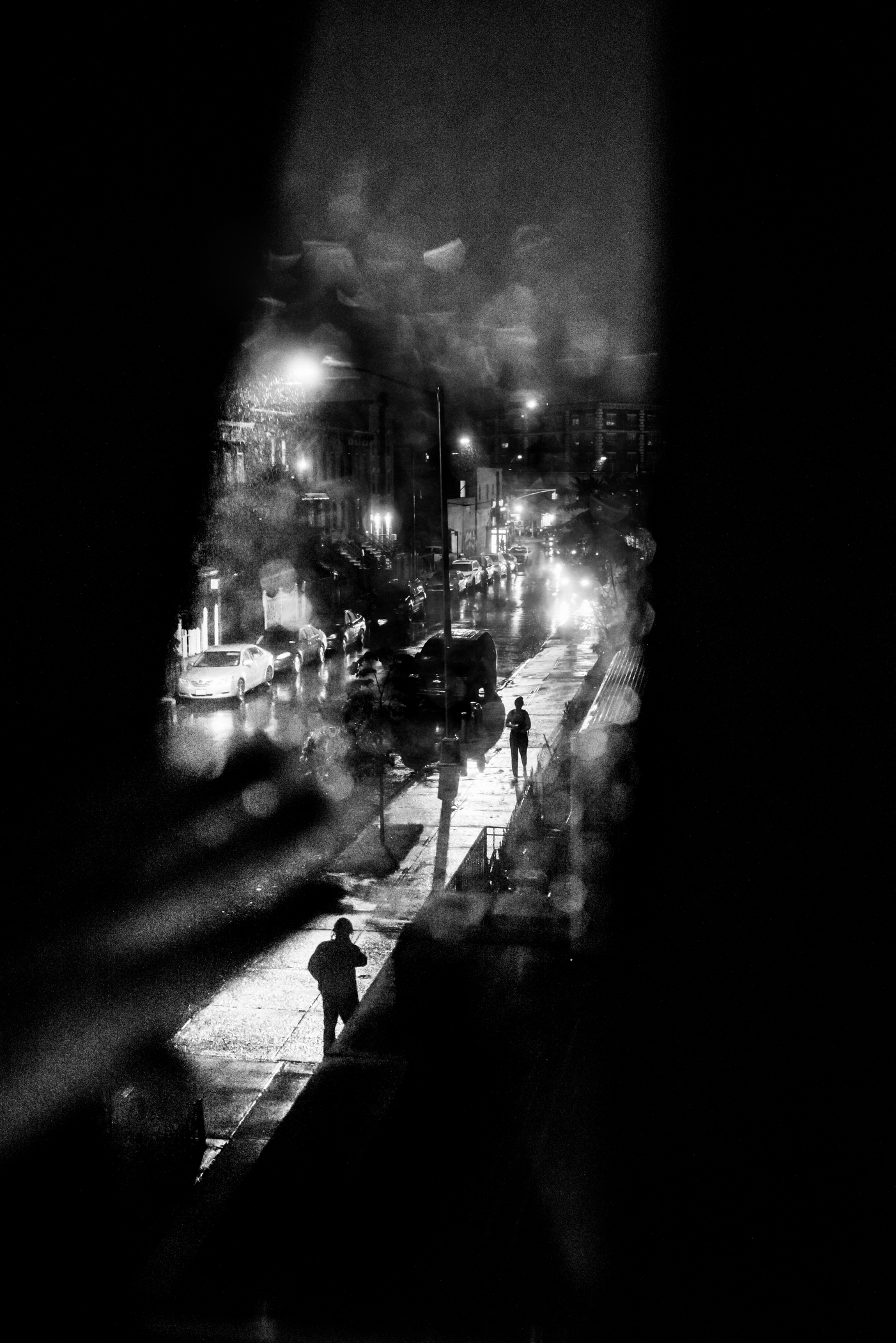 People walk towards each other, through the rain, down Kossuth Place between Bushwick Avenue and Broadway in Bushwick, NY.
