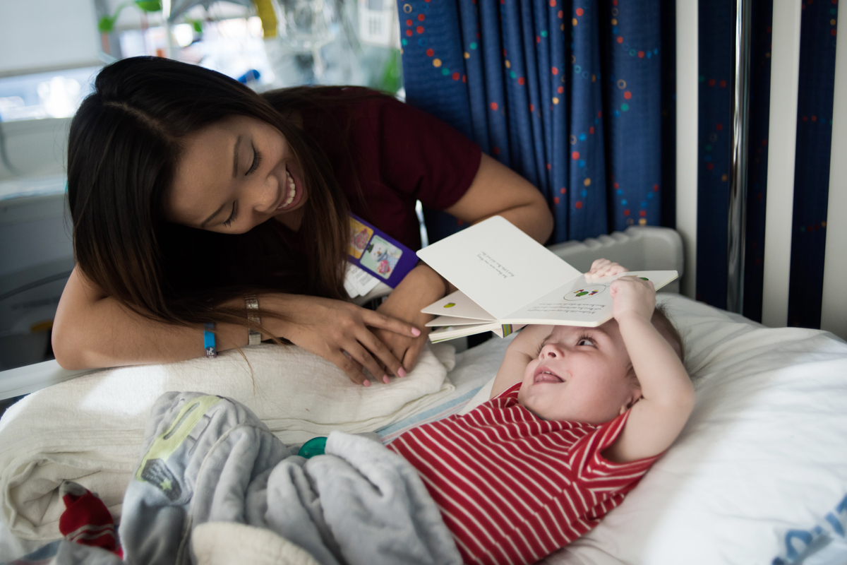 Nursing attendant Jenny Bui looks at Jadon McDonald as he plays with a book at Montefiore Children's Hospital in The Bronx, New York, N.Y. on December 14, 2016.