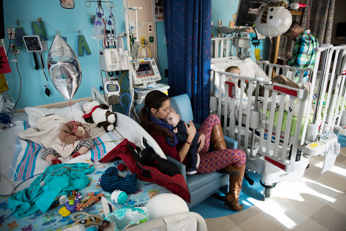 Nicole McDonald holds her son Anias as his twin Jadon sleeps (left) and oldest son Aza watches television at Montefiore Children's Hospital in The Bronx, New York, N.Y. on December 14, 2016.Credit: Mark Kauzlarich for CNN