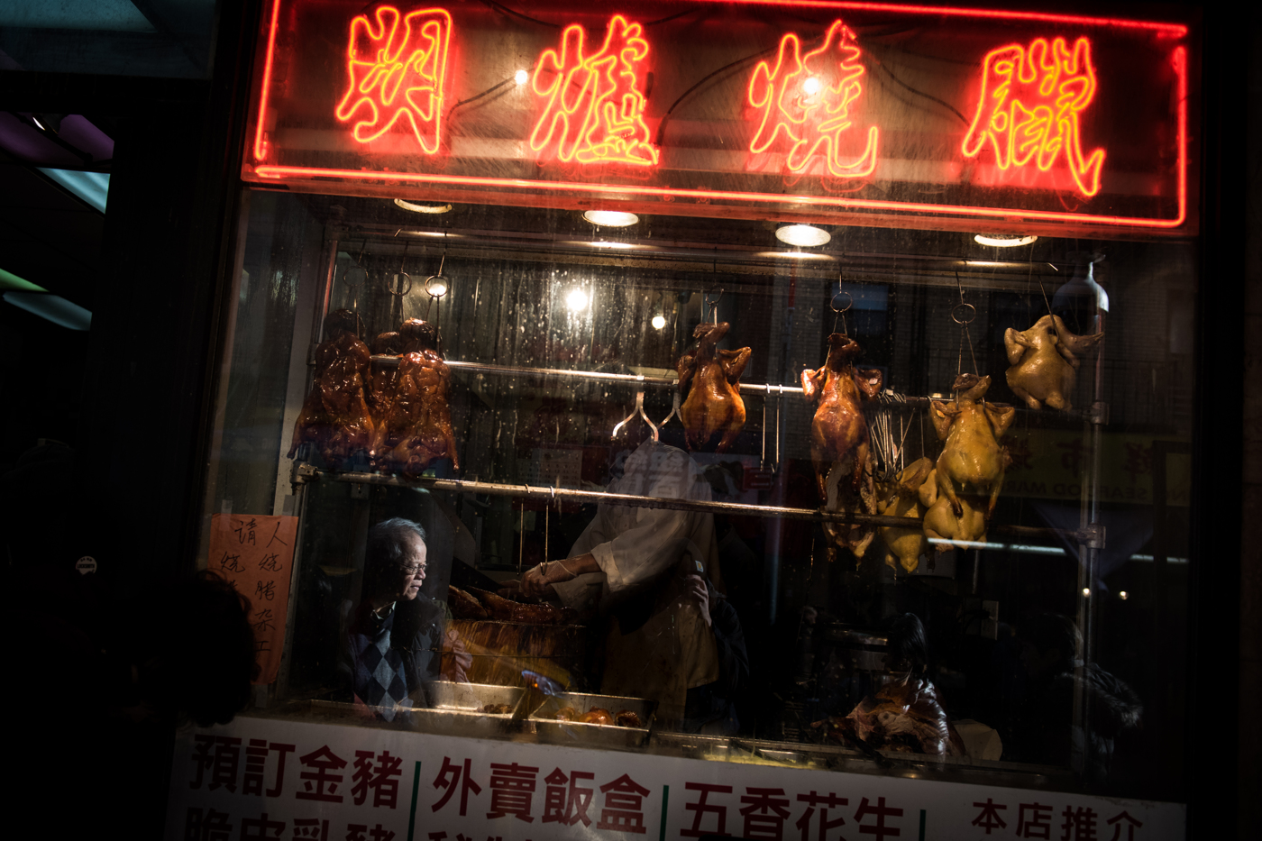 An elderly man is reflected in the window of a restaurant in a neighborhood busy with people shopping in preparation for Chinese New Year in the Chinatown neighborhood of Manhattan in New York, NY.