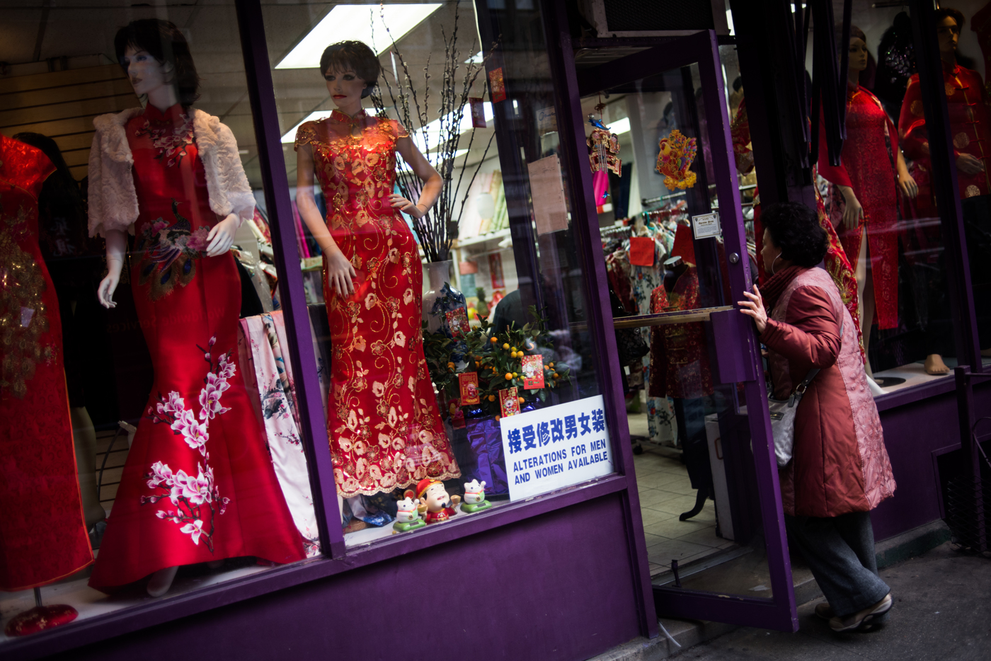 A woman enters a store selling traditional clothing in Chinatown New York, NY.
