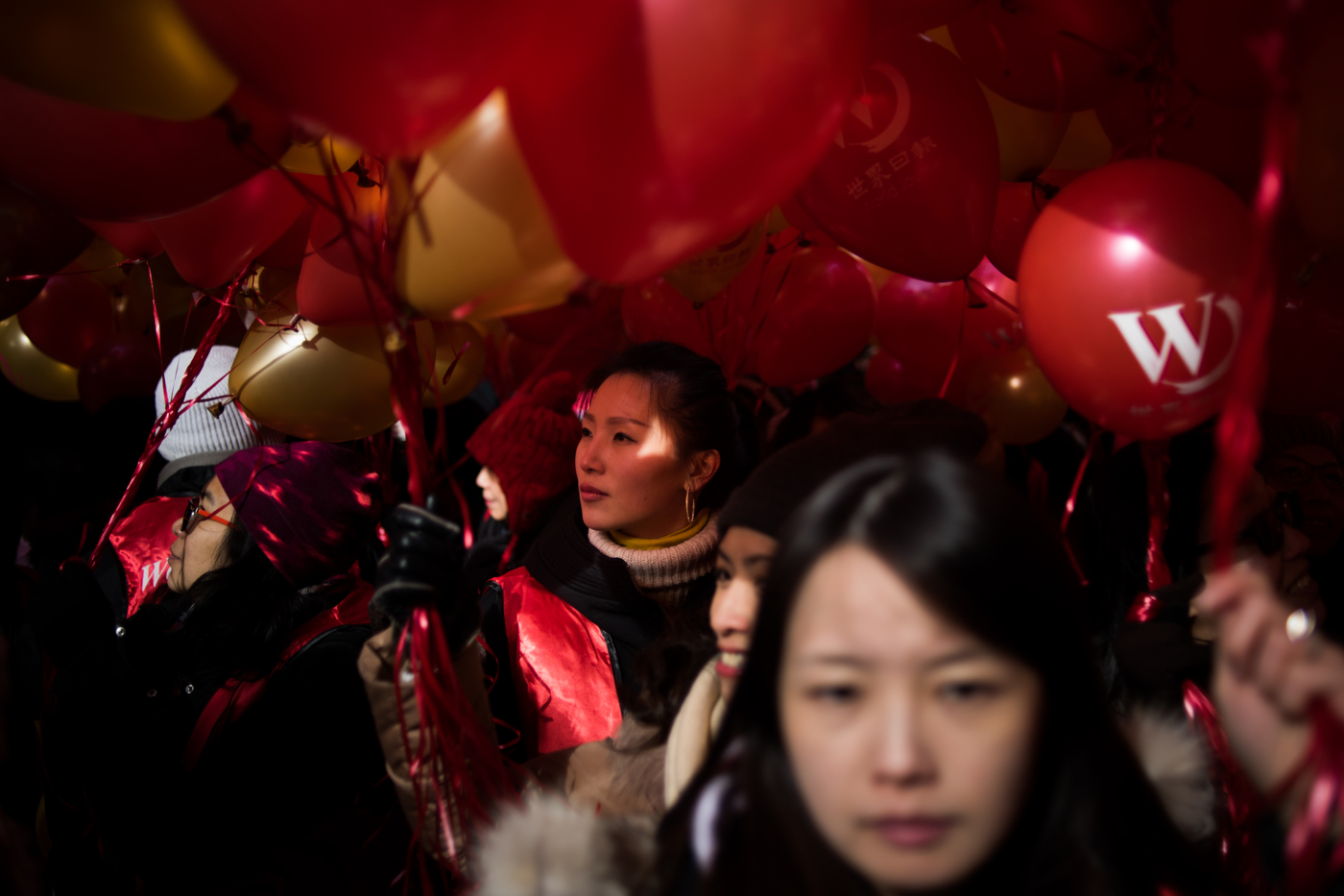 A woman gazes through a field of balloons while waiting for the start of the Chinese New Year Parade in the Chinatown, New York.