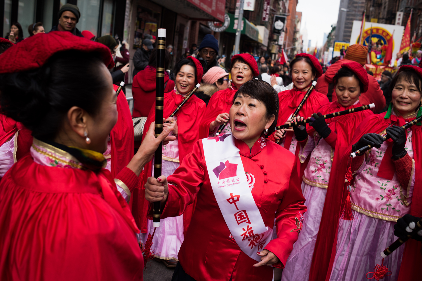 A woman chides one of the participants of her parade group while preparing for the Chinese New Year Parade in the Chinatown neighborhood of New York.