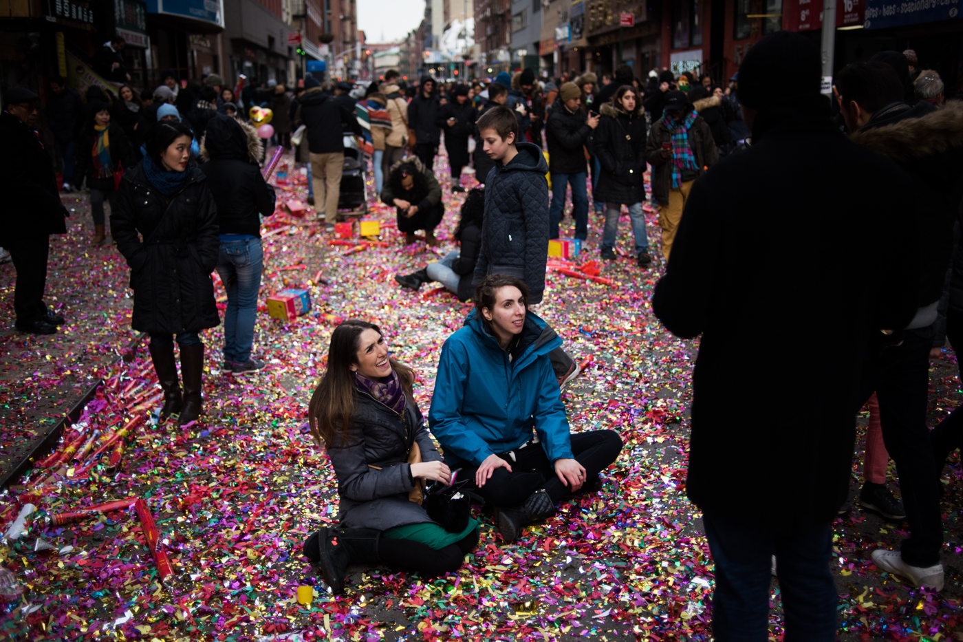 People sit in a street filled with confetti during the Chinese New Year Parade in the Chinatown neighborhood of New York.