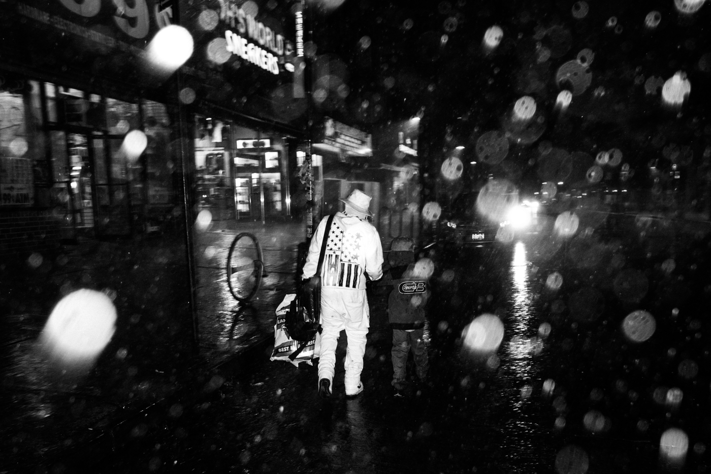 A man walks with a child down Broadway through a springtime rainstorm in Bushwick. This section of Broadway, from here to a few blocks further south, saw four shootings in one week, which one NYPD officer said was likely related to gang initiations and retaliations.