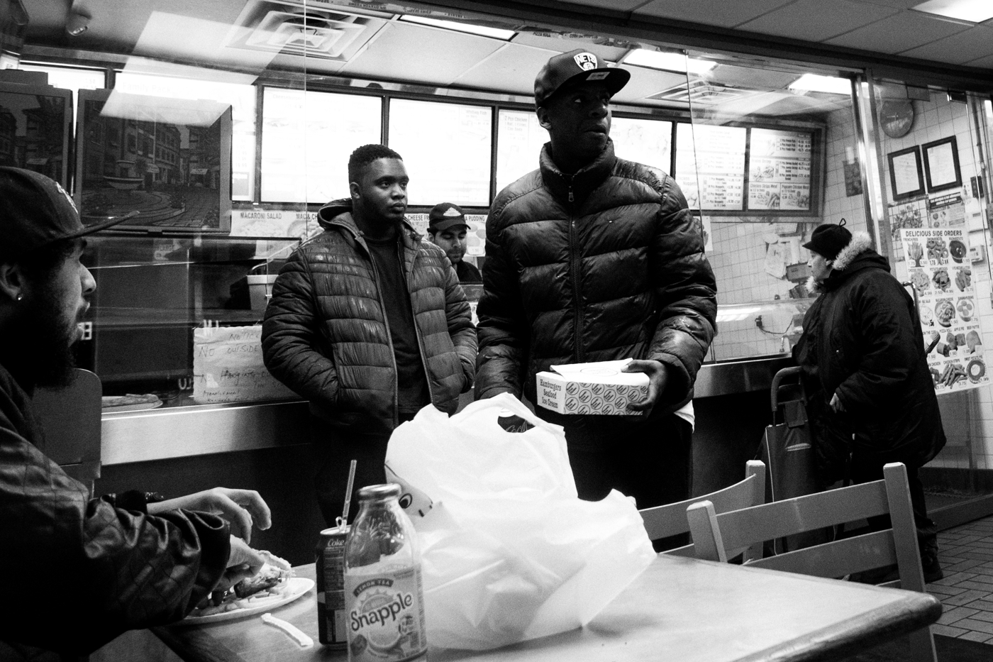 People eat and wait for their orders at the Kennedy's Fried Chicken shop on Broadway on the border between Bushwick and Bed-Stuy in New York.