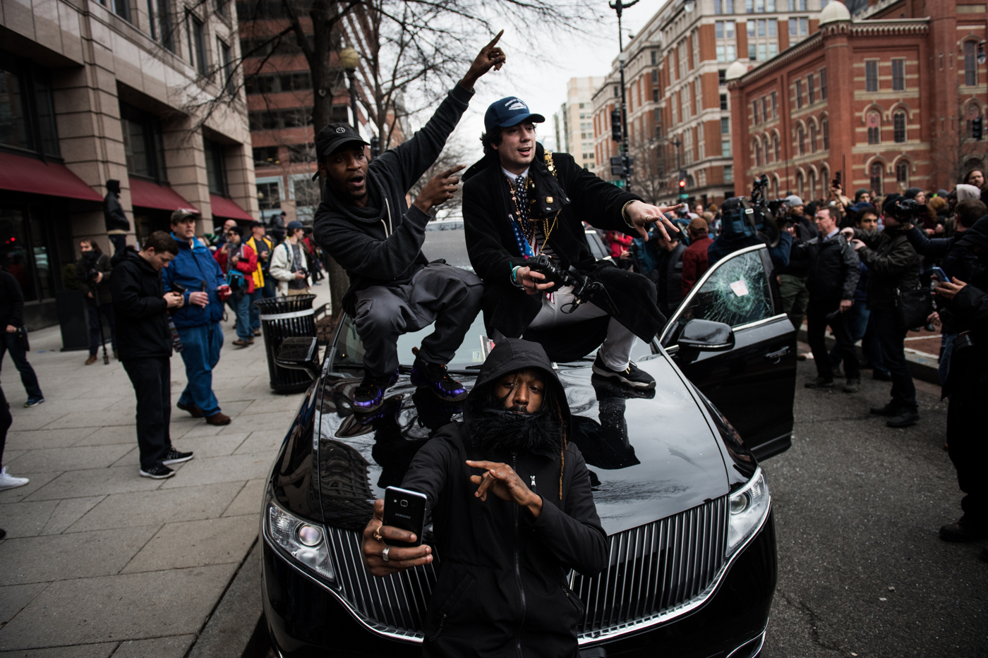 People dance on a destroyed limousine for cameras filming them after Donald Trump's inauguration as the 45th President of the United States in Washington, D.C., on January 20, 2017. Credit: Mark Kauzlarich for CNN
