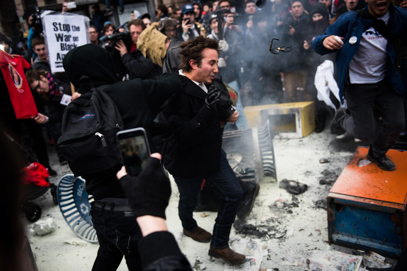 A supporter of President Donald Trump (center) is punched in the face by anarchist protestors after having his hat stolen after Trump's inauguration as the 45th President of the United States in Washington, D.C., on January 20, 2017. The supporter had been talking to the crowd after he put out a fire started during the protests. Credit: Mark Kauzlarich for CNN