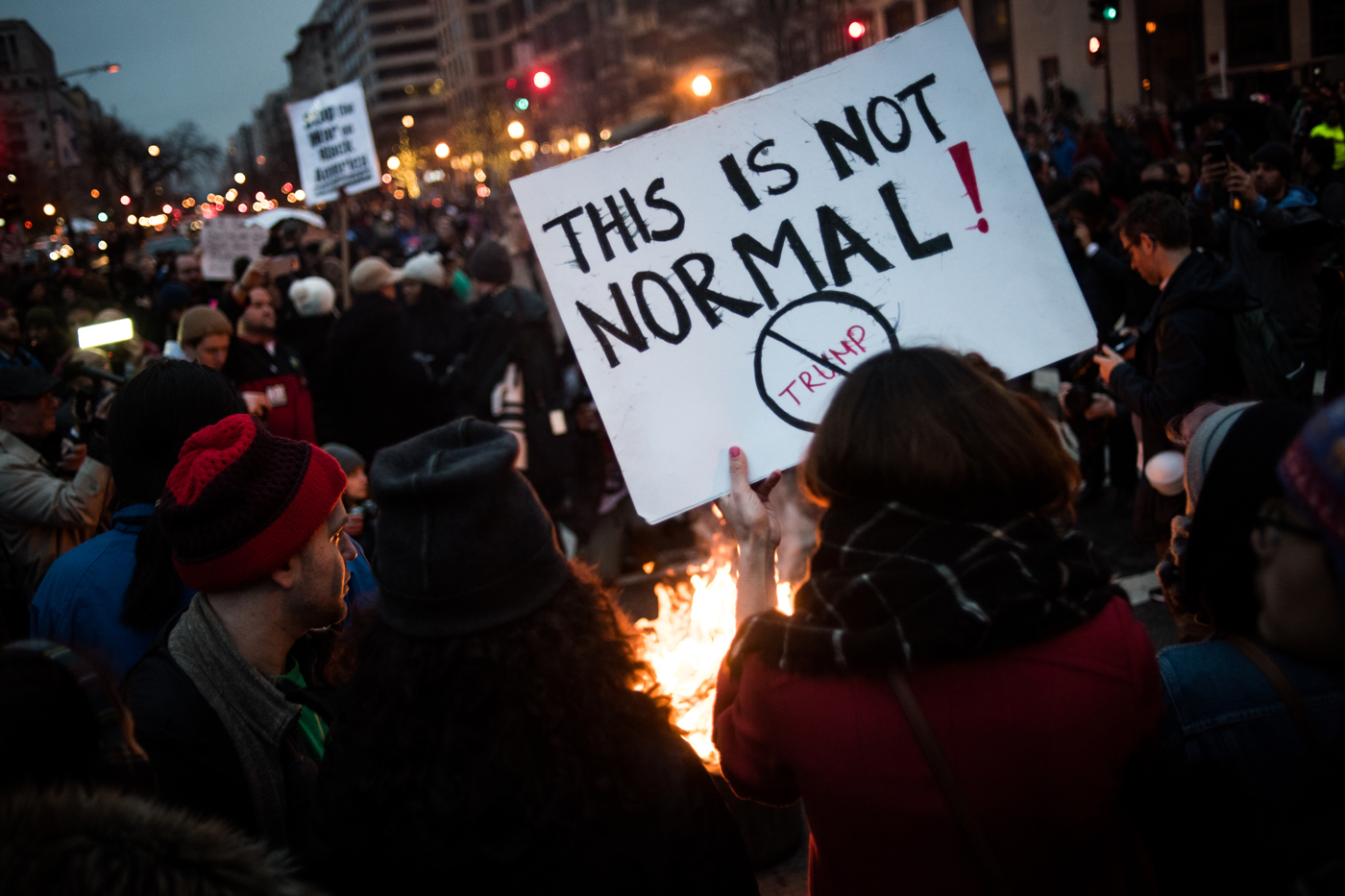 A woman holds a sign near a fire started to protest Donald Trump's inauguration as the 45th President of the United States in Washington, D.C., on January 20, 2017. Credit: Mark Kauzlarich for CNN