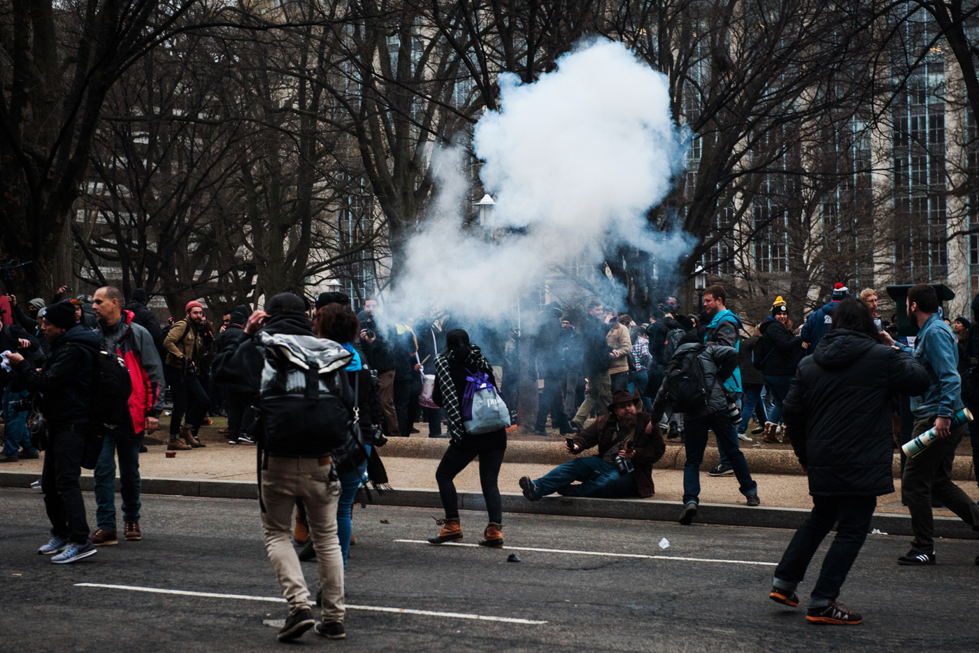 People react to a flash bang grenade fired by D.C. Metropolitan Police Officers during protests against Donald Trump's inauguration as the 45th President of the United States in Washington, D.C., on January 20, 2017. Credit: Mark Kauzlarich for CNN