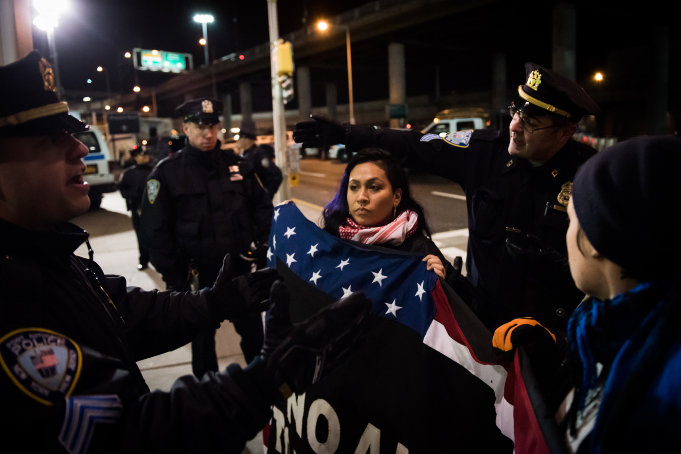 Port Authority police officers try to move a woman carrying a flag at John F. Kennedy International Airport in New York, NY on Saturday, January 28, 2017. Credit: Mark Kauzlarich for CNN