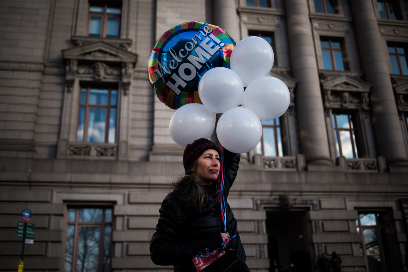 Dawn Eshelman holds balloons, symbolically welcoming refugees, prior marching from Battery Park to Federal Plaza in the Manhattan borough of New York, NY on Saturday, January 29, 2017. Credit: Mark Kauzlarich for CNN