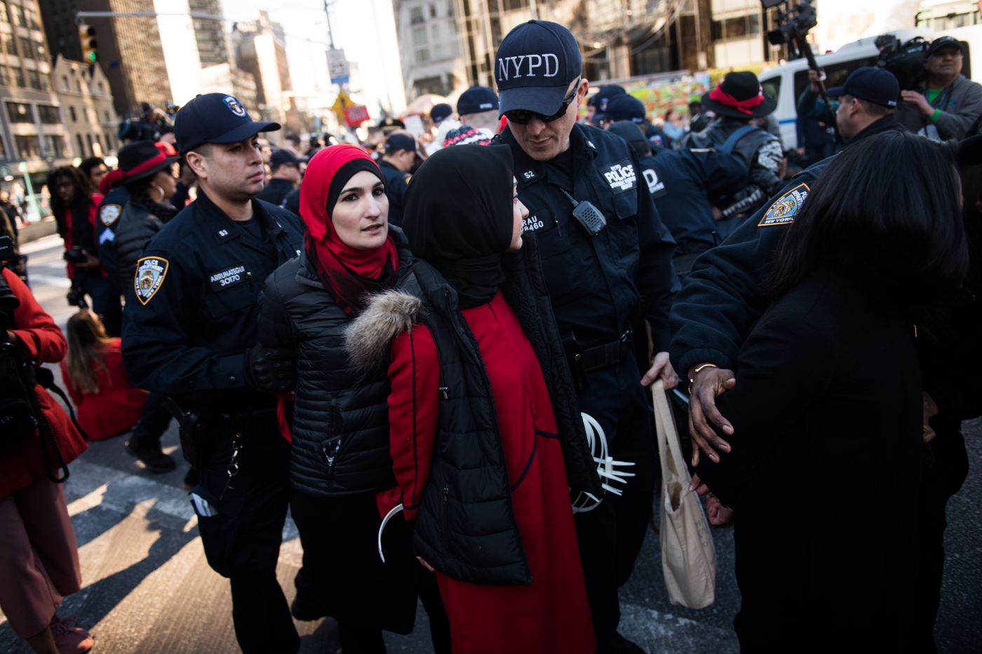 Linda Sarsour, left, is arrested for blocking traffic in Columbus Circle during an International Women's Day rally and march in New York, NY on March 8, 2017. CREDIT: Mark Kauzlarich for CNN