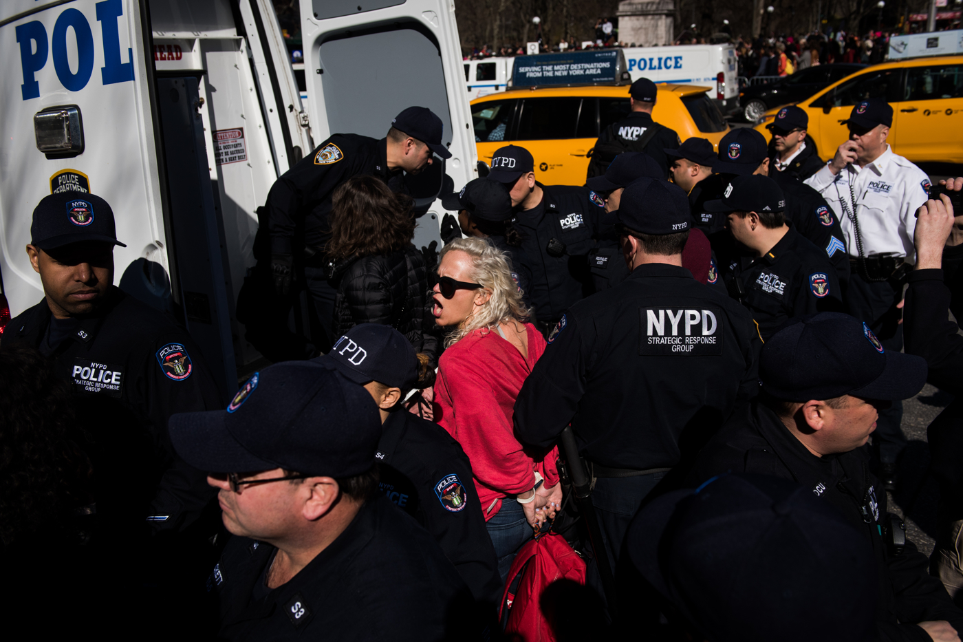 Demonstrators are loaded into a police van after being arrested for blocking traffic in Columbus Circle during an International Women's Day rally and march in New York, NY on March 8, 2017. CREDIT: Mark Kauzlarich for CNN