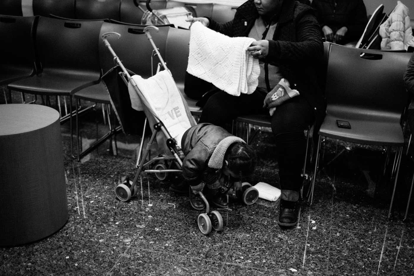 A baby leans over in a stroller as his mother waits to speak with a lawyer at Catholic Charities Community Service's walk-in immigration aid day in New York, NY on March 9, 2017. CREDIT: Mark Kauzlarich for CNN