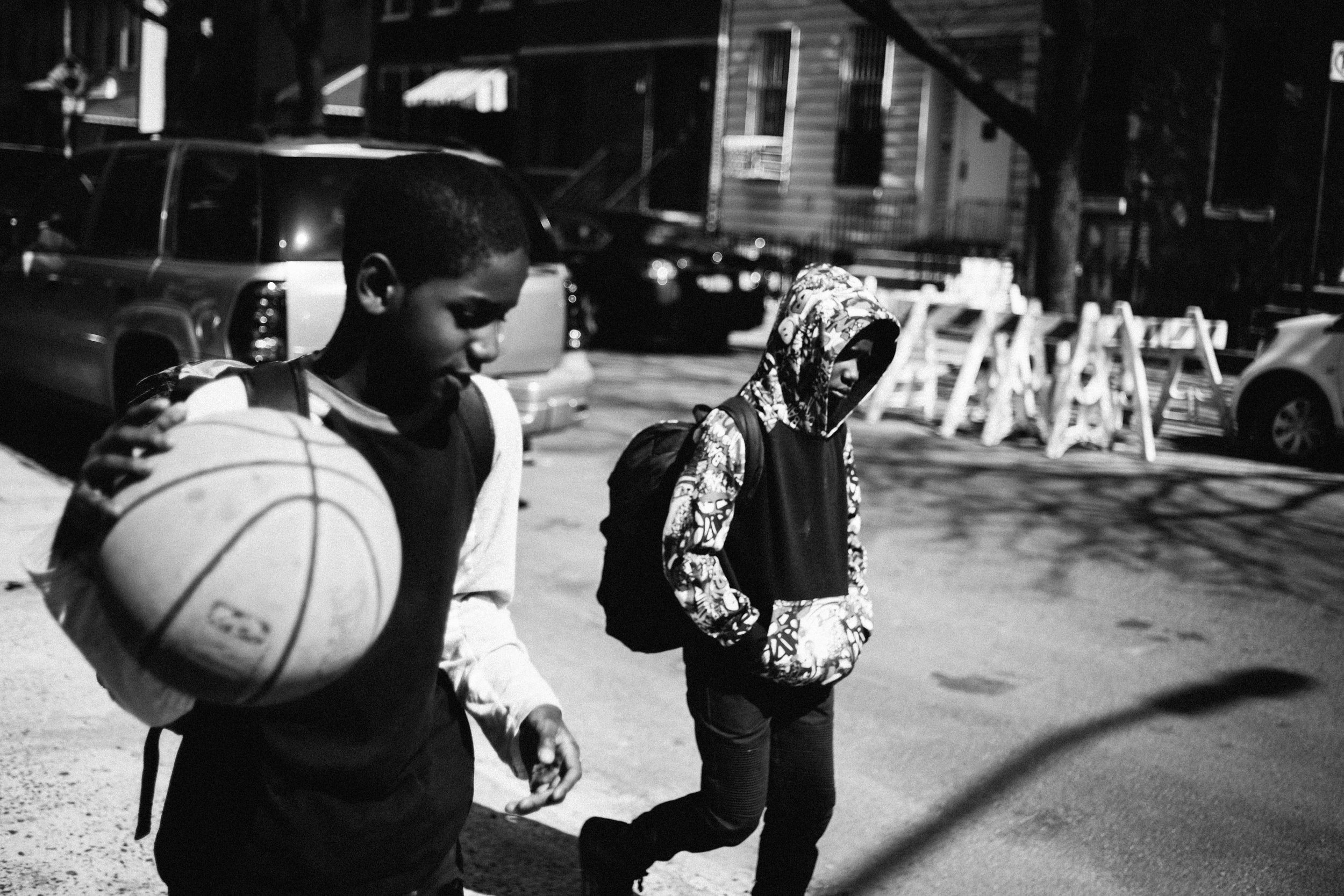 Two young men walk home from school in Bushwick.