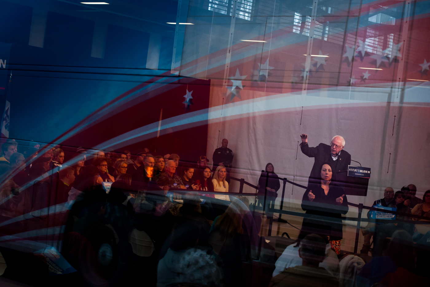 The reflection of the campaign bus for U.S. Democratic presidential candidate Bernie Sanders is reflected in a window as he speaks at a town hall in Iowa Falls, Iowa January 25, 2016.