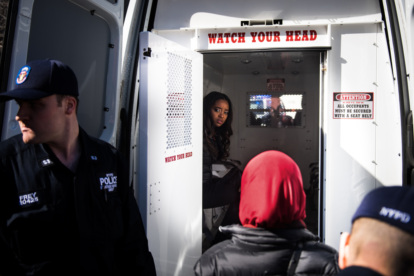 Tamika Mallory, National co-chair of the Women's March, sits in the back of a police van after being arrested for blocking traffic in Columbus Circle during an International Women's Day rally and march in New York, NY on March 8, 2017.