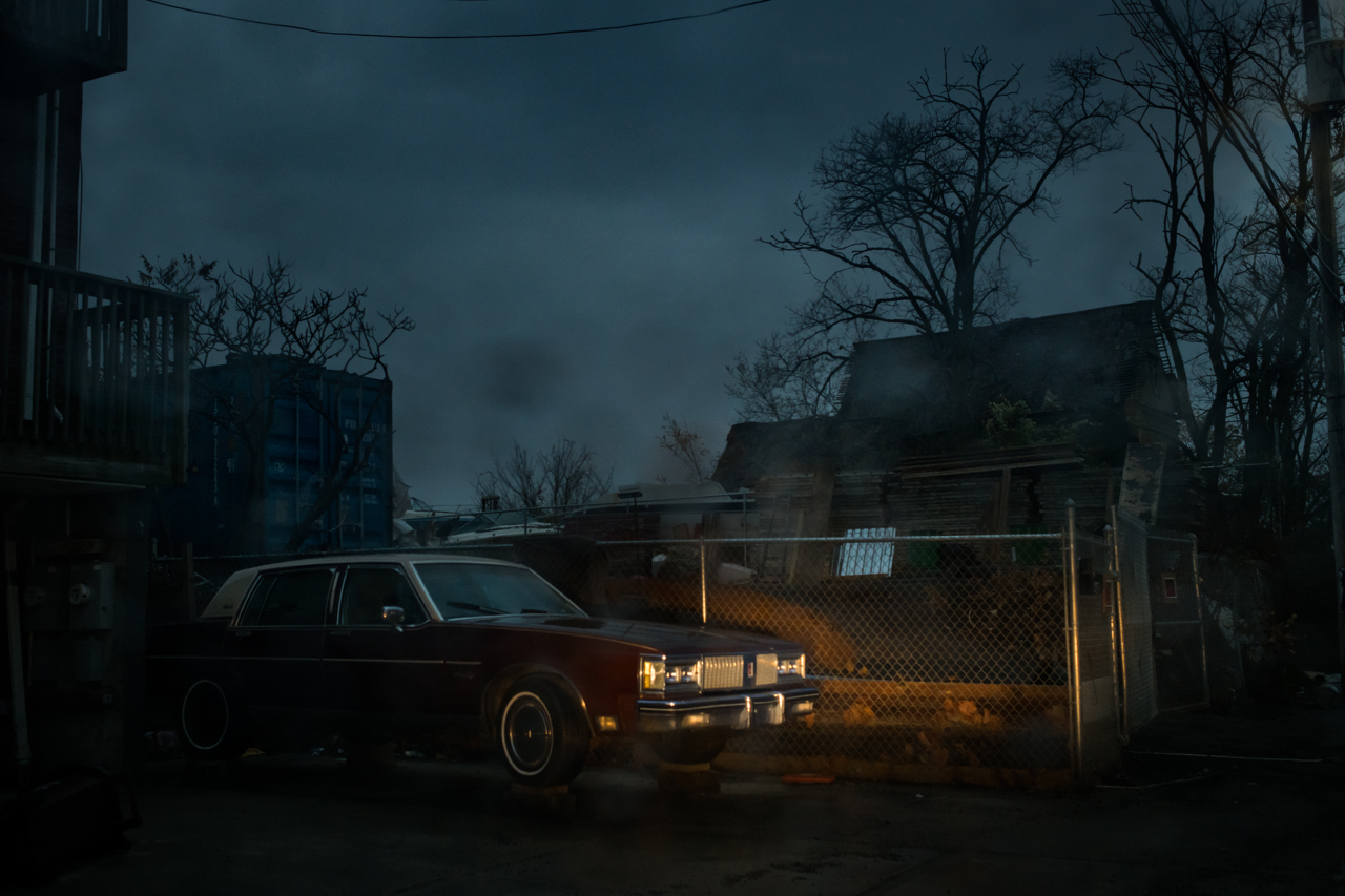 A 1980s Oldsmobile sits up on wood blocks in a low income neighborhood of Rockaway, Queens, NY. This block and the one next to it were designated by the Department of City Planning as needing further planning for adaptation over time.