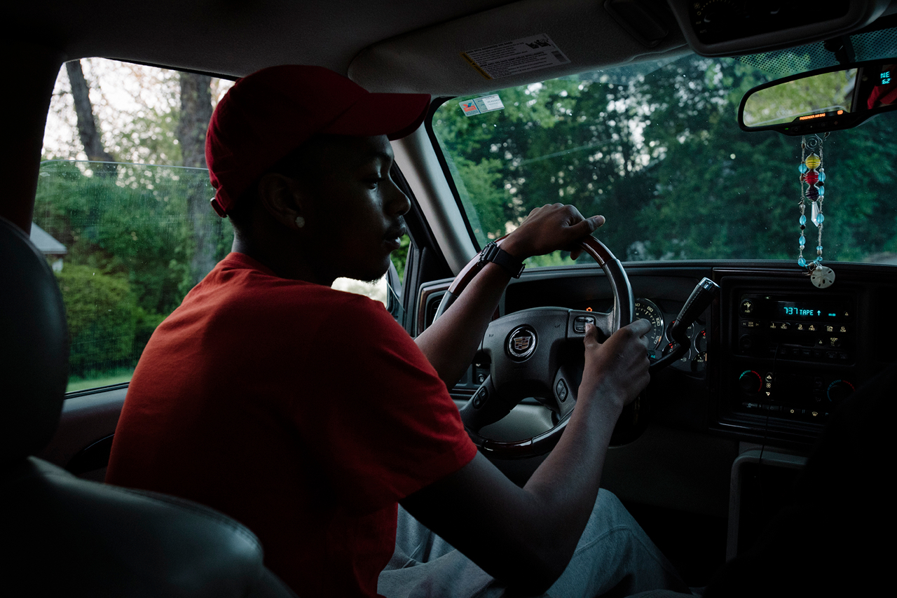 Redd waits for a friend in his Cadillac Escalade before going to the liquor store to buy more Hennessey. Despite the common narrative of absent parents and risky behavior, Redd and his friends hang out on the street outside one of their parent's house.