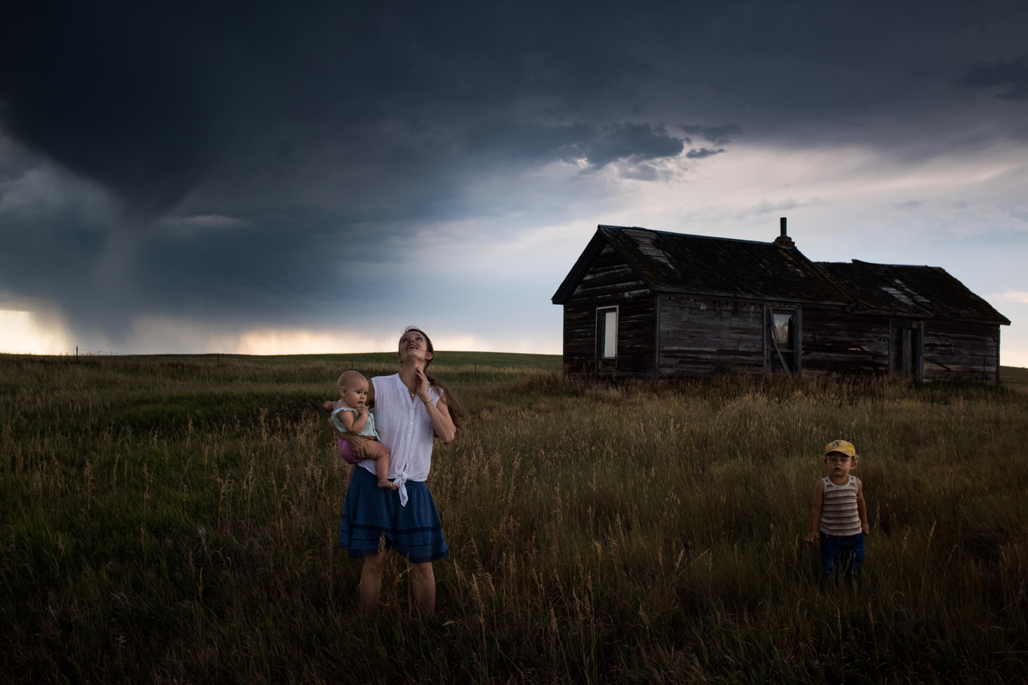 """45�33'14.2""""N 102�30'36.1""""W. 114 miles from the nearest McDonald's.Eliza Blue holds her daughter Emily as her son Max closes his eyes and feels the coming storm winds on his face as they stand near an abandoned farmhouse on their leased land in Meadow, SD on July 31, 2017. Ranchers and farmers have spent much of the droughty summer watching clouds on the horizon, hoping storms would hit, but most pass by without rain."""