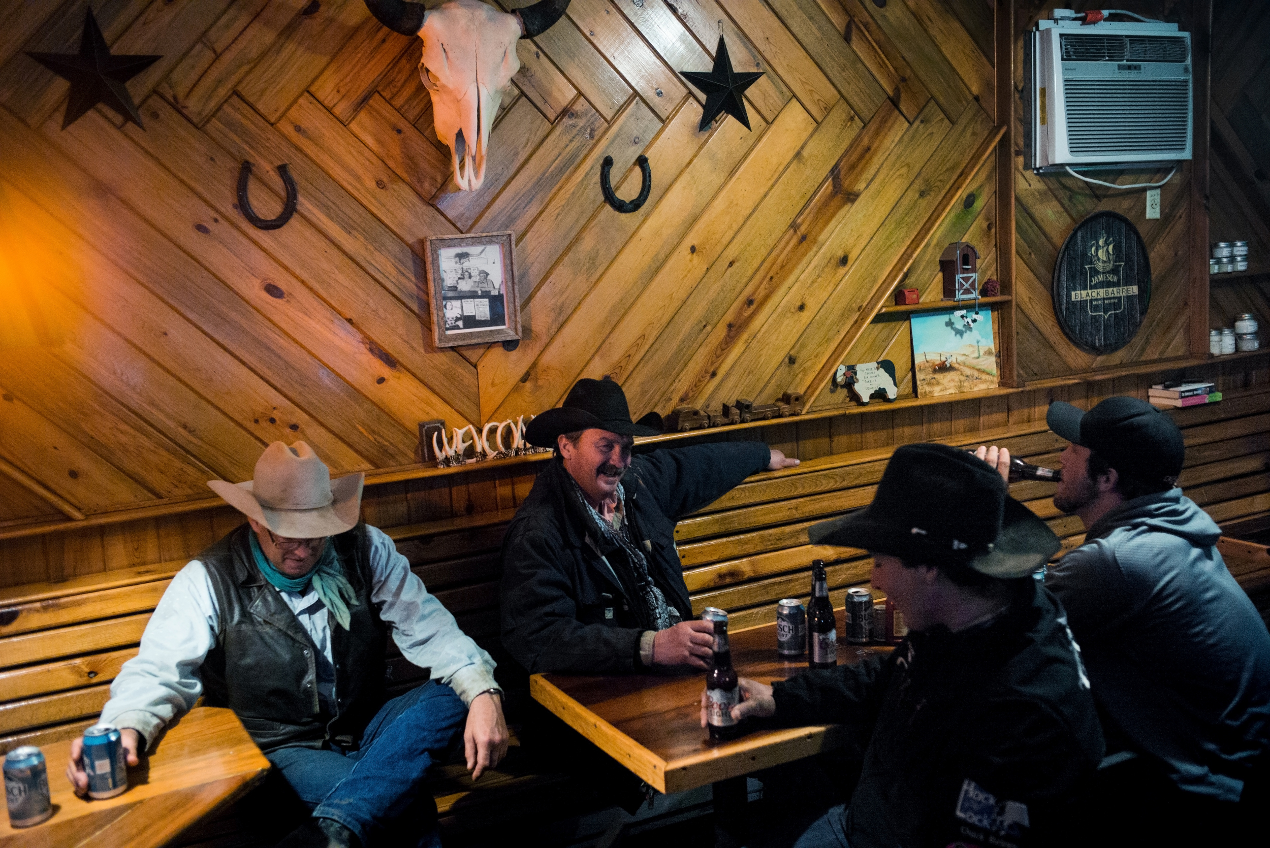 "45º31'48.9""N, 102º12'59.8""W. 123 miles from the nearest McDonald's.  Men drink at Smoky's Bar and Grill during an uncommon break during the spring calving season in Meadow, SD on April 15, 2018. Winter has dragged on into mid-April in South Dakota and ranchers spent many days preparing for an incoming winter storm that brought back memories of storms in 2013 and 1997 that killed hundreds of thousands of cattle and drove some to suicide."
