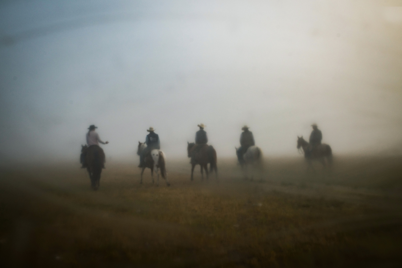 """45º25'37.9""""N, 102º17'10.7""""W. 113 miles from the nearest McDonald's. The Arneson family and their employee Riley Cihak ride their horses through thick morning fog on their ranch in the old town of Chance, SD on July 31, 2017. The Arnesons family moved from Montana to South Dakota due to rising land prices and taxes and slowly accumulated the entirety of what was once a small town in the area with a post office until the late 1950s."""