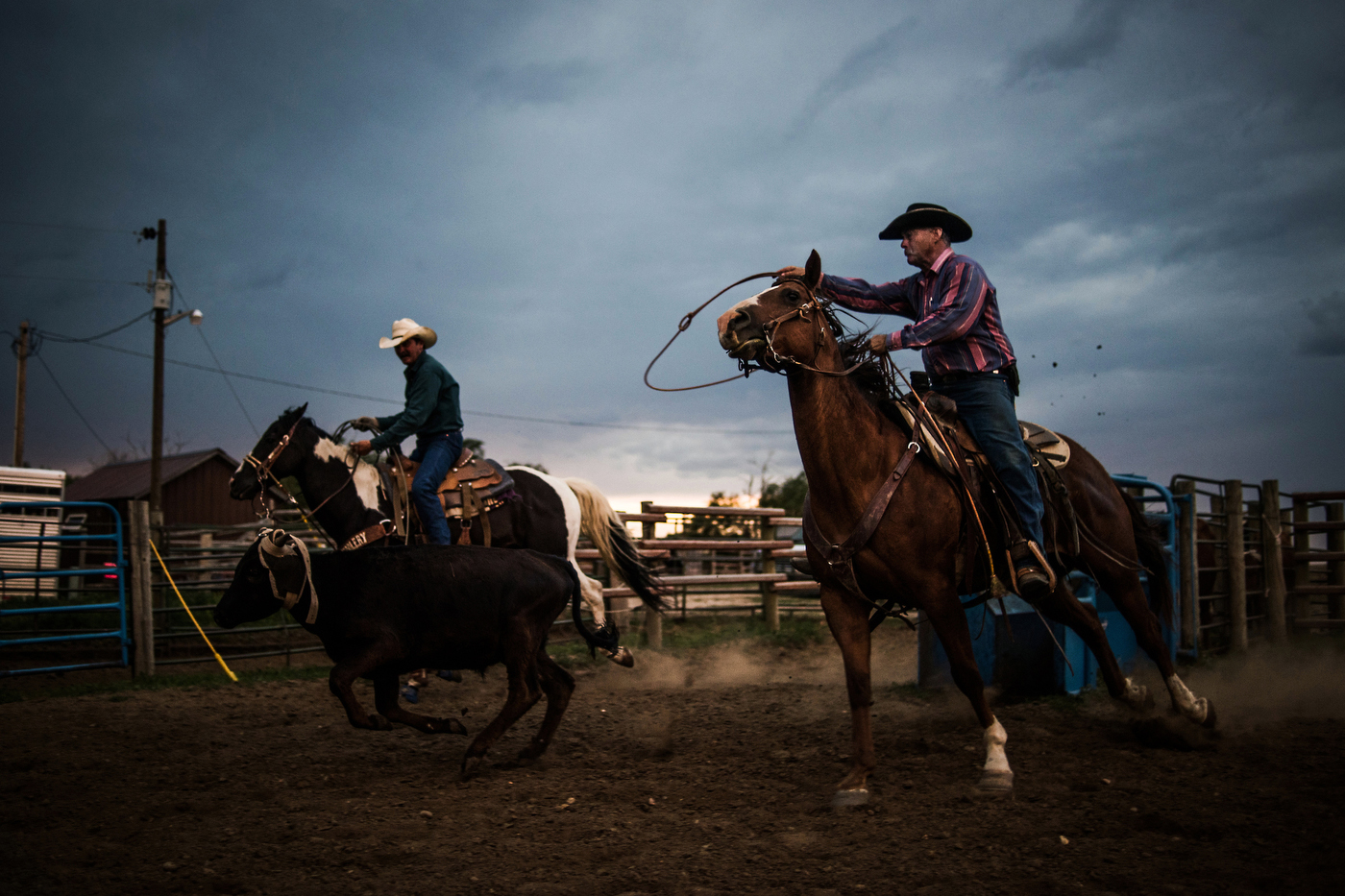 """45º31'58.9""""N, 102º15'19.0""""W. 121 miles from the nearest McDonald's. Scott Storm swings a rope as he practices team roping with his friend Kenny Kocer at Kocer's ranch in Meadow, SD. Storm was known as a great roper on teams years ago but stopped after he was married; he didn't rope again until his son was old enough to start."""