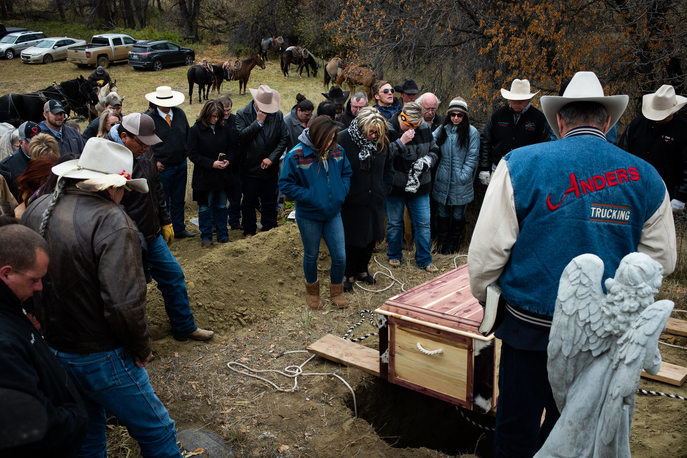 Mourners gather around the grave of Gregg Seim, 61, during his internment at the Seim Family Cemetery in Shadehill, SD.