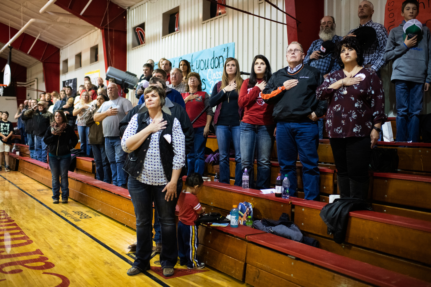 People stand for the national anthem at the Bison Cardinals varsity volleyball game against Mott-Regent High School in Bison, SD.