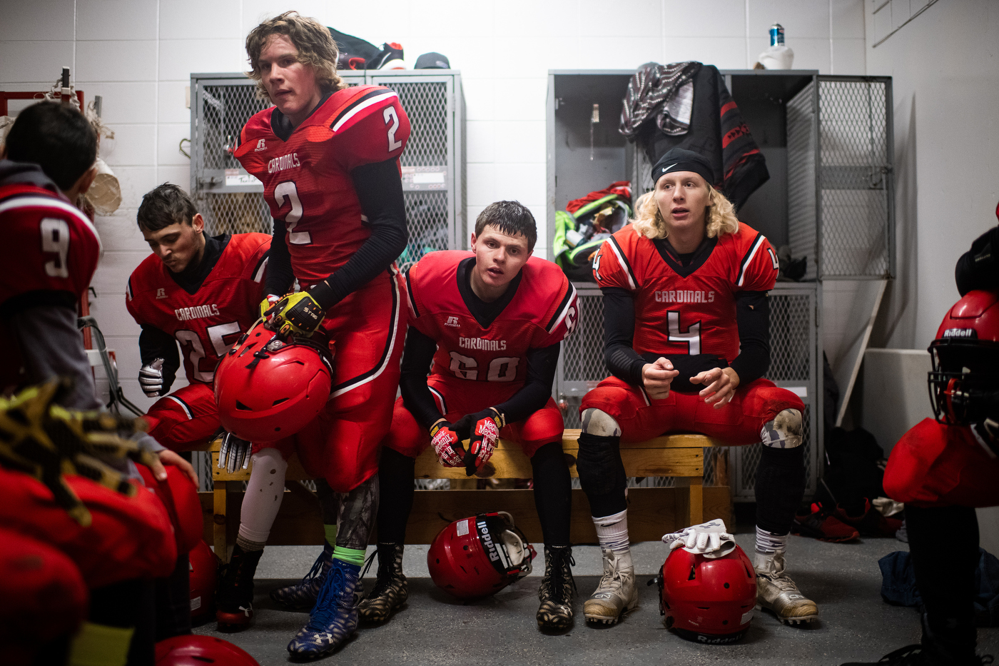 Players take a break in a high school locker room during the Bison Cardinals' game versus northern rivals, the Lemmon-McIntosh Cowboys in Bison, SD.