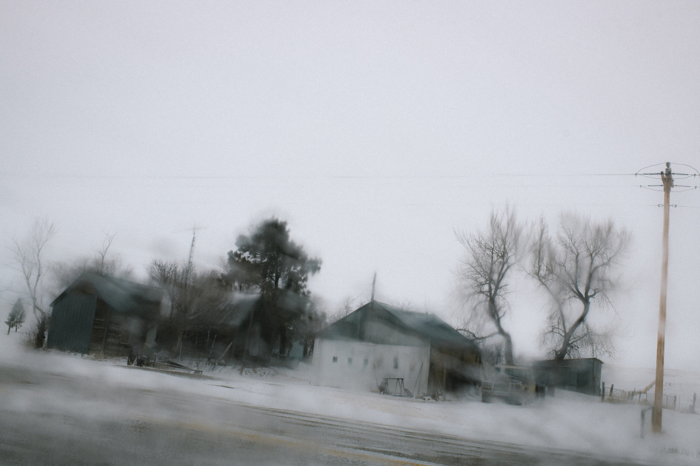 """45º31'48.9""""N 102º12'59.8""""W. 123 miles from the nearest McDonald's.  A derelict ranch, neglected for 7 months after it's owner died last July, is seen through the icy window of a car after an early-spring snowstorm in Meadow, SD on April 8, 2018. Perkins County has lost 74% of its population since 1910 and in the past 7 months, four residents of Meadow have died, lowering the population by 11% in less than a year."""