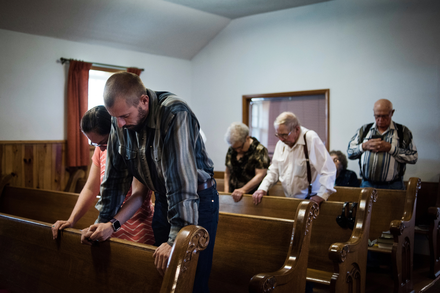 """45°26'49.9""""N 102°10'07.6""""W. 127 miles from the nearest McDonald's.  Parishioners pray while worshiping at Coal Springs church in Meadow, SD. While many old prairie churches have closed over the years, many other small congregations still struggle to survive, or have multi-point parishes with one pastor serving a large area."""