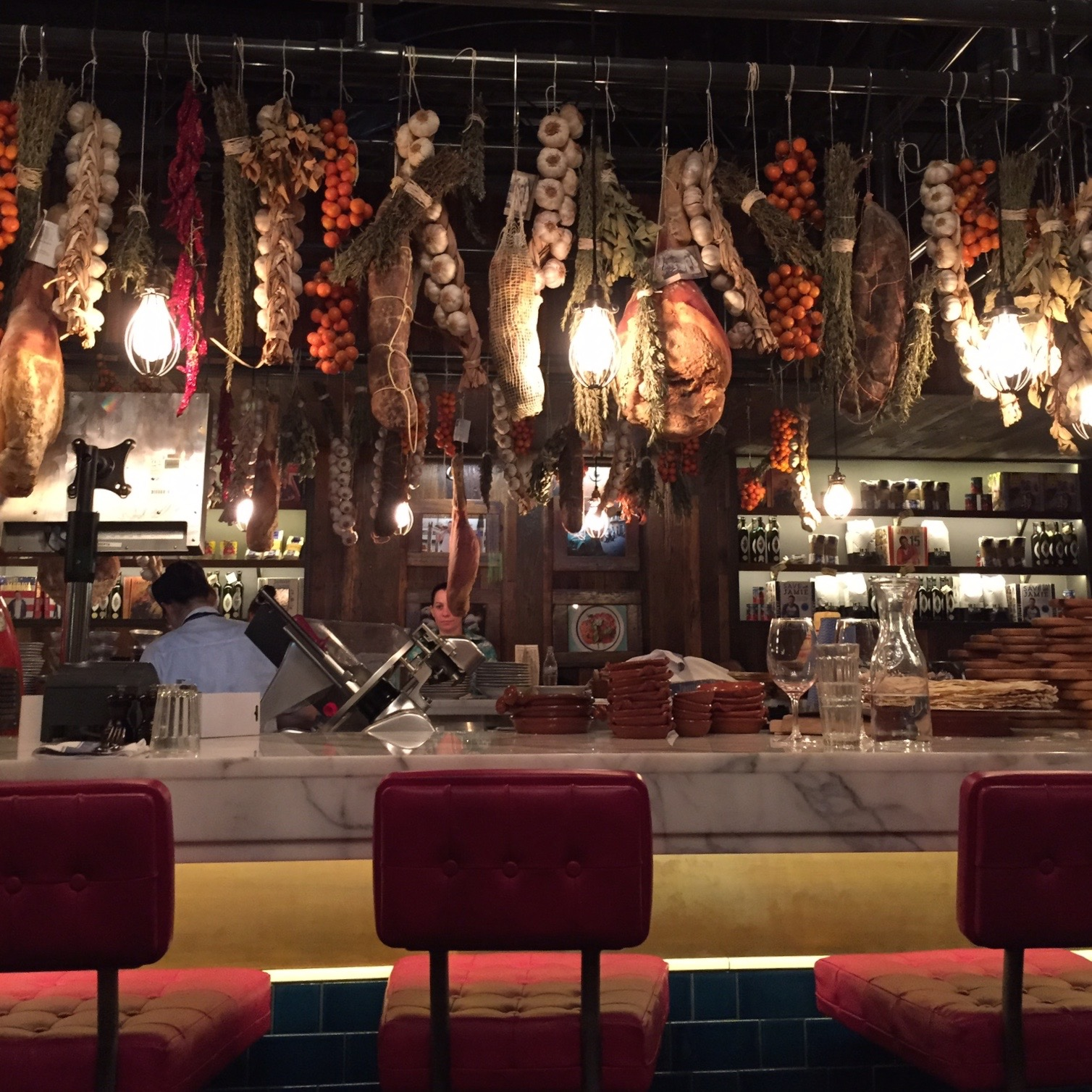 Real displays of cured meats and veggies hang over the bar seating at Jamies