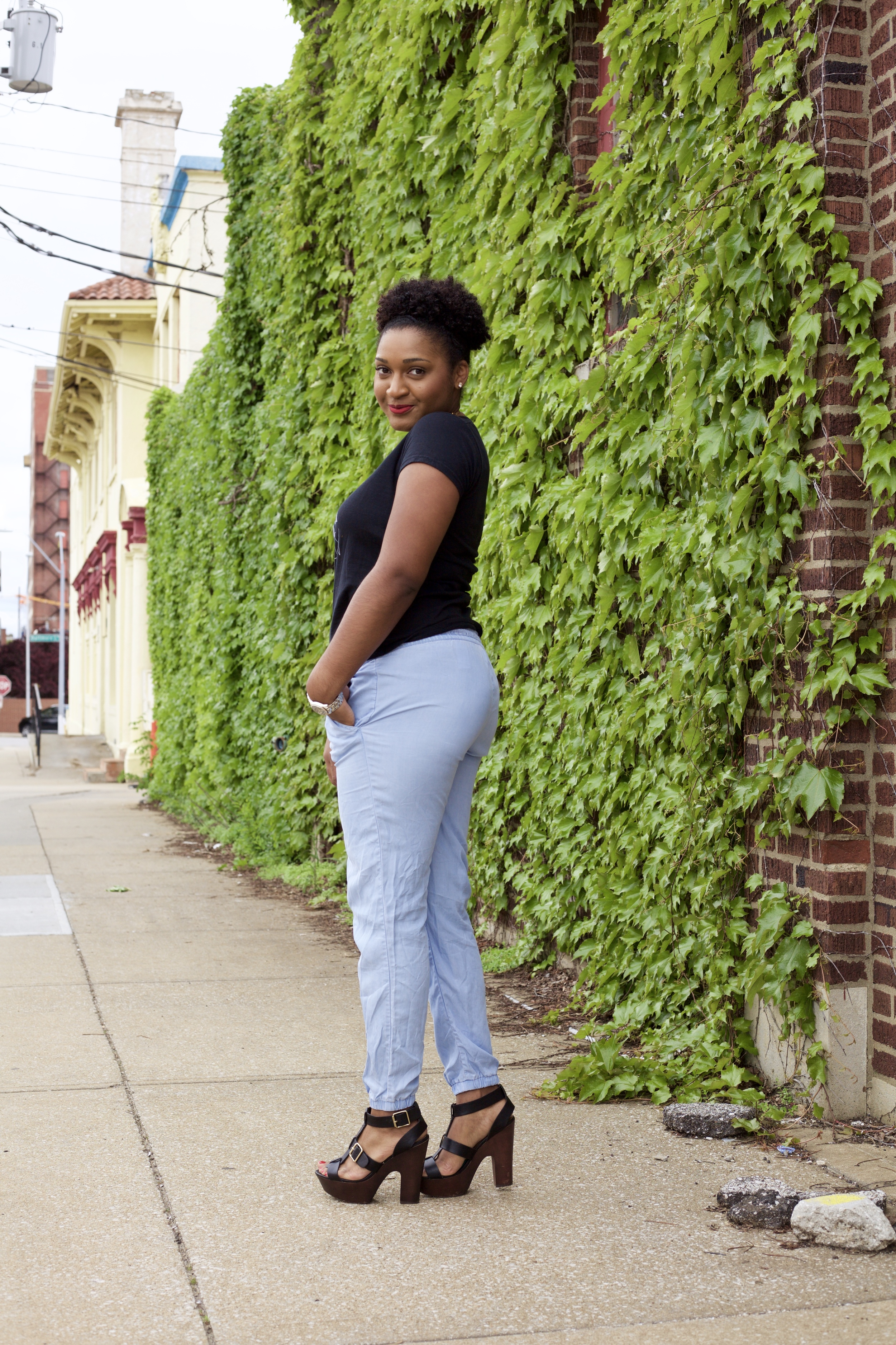 Blogger, Jasmine Cooper of jasminediane.com, wearing a black top and jean joggers with heels and a statement necklace,