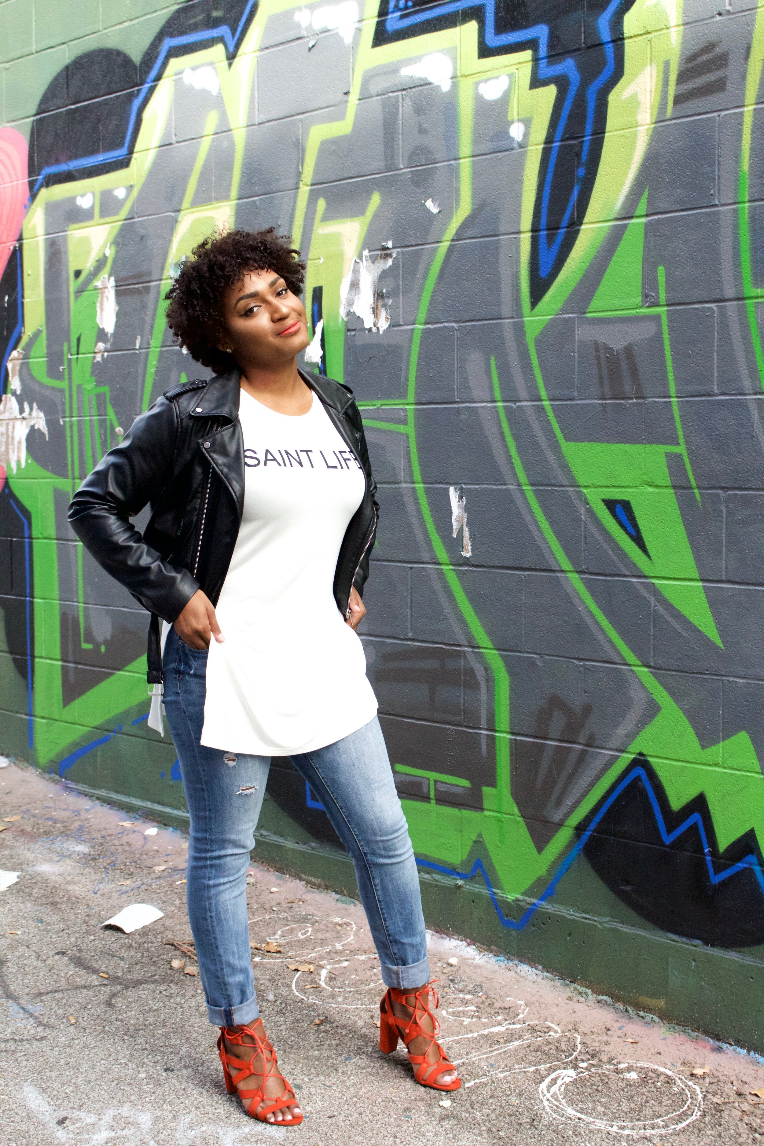 Leather Jacket, saint life tee, Orange Strappy Heels and distressed jeans by black fashion blogger jasmine diane.