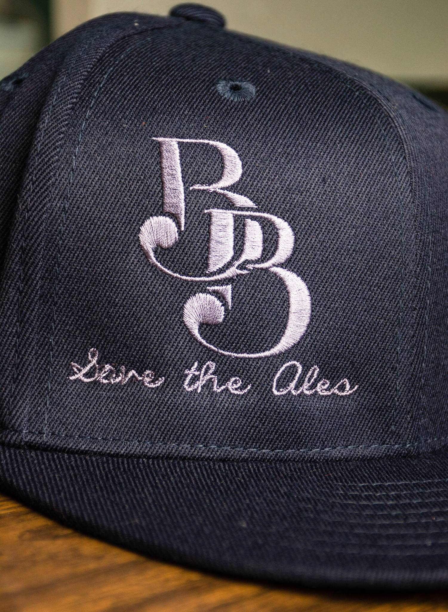 "Fitted Caps   Close-up shot of Boundary Bay's navy ""BB Fitted Cap"" I designed these fitted caps to include Boundary Bay's signature  BB  logo with their  Save The Ales  slogan underneath. Back of the cap reads  Brewed in Bellingham, WA.  The embroidery is purposely off-centered to the right (because that's the cool thing to do these days)."