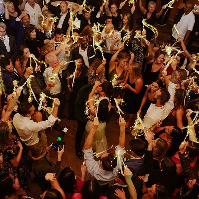 """Throwing it back to this beautiful """"last dance"""" and """"grand exit"""" at Indy and Chad's recent wedding.😃🎶❤️  . Lighting enhances everything. Our custom-designed amber uplighting with the bride and grooms twinkle lighting wands not only looked incredible in wedding photos and videos, but it also gave Indy and Chad's guests a fun way to participate during these two special moments of their wedding. Definitely, something fun to consider for your special day! ✨✨✨ . Indy and Chad also incorporated one of our incredible open-air photo booth machines during the reception. Our professional studio-lighting, skin-smoothing glamour filters, and our black sequin backdrop made everyone look amazing.  Many of our clients photo booth photos end up being used for their annual holiday cards, wedding """"thank you"""" cards, calendars, and other fun gifts. 🎁🥰 . Venue: @nestldownevents  SEM: @devromma  DJ: @losgatosdj  Photo Booth: @losgatosphotobooth  Caterer: @poetryinmotioncatering  Photographer: @danipurington  Florals: @asieldesign   #nestldown #nestledown #nestldownwedding #theknot #stylemepretty #weddinginspo #weddinginspiration #junebugweddings #heyheyhellomay #greenweddingshoes #huffpostido #loverly #buzzfeedweddings #radlovestories #loveandwork #risingtidesociety #pursuepretty #thatsdarling #darlingmovement #inlove #flashesofdelight #losgatosdjcompany #losgatosdjs #losgatosdj #losgatosphotobooth #tbt"""