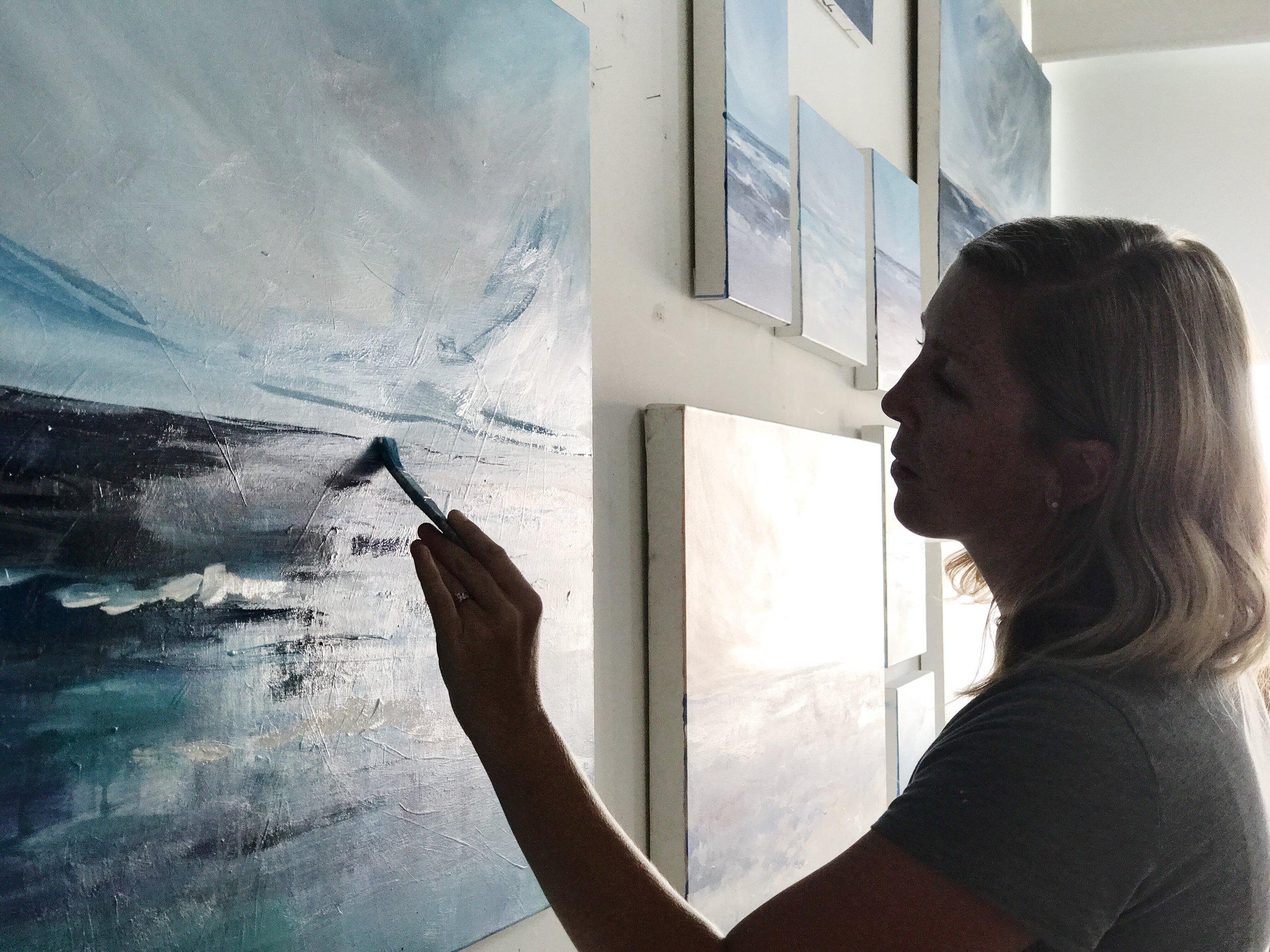 Megan Elizabeth painting an ocean in her studio in NYC