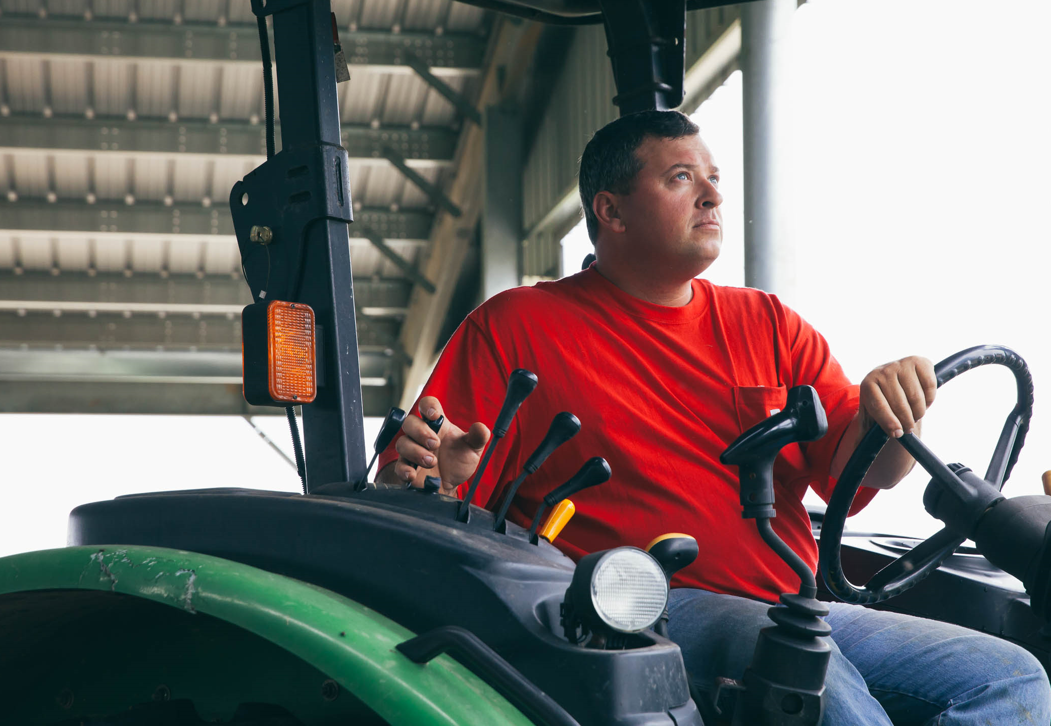 Brandon Oliver runs the tractor through the Composting Barn